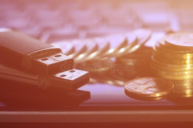 USB minneskort och några mynt som framme ligger på kroppen av den svarta bärbara datorn av hans tangentbord Lagring för faktiskt  arkivfoton