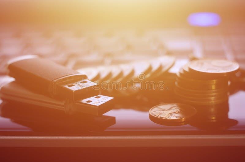 USB minneskort och några mynt som framme ligger på kroppen av den svarta bärbara datorn av hans tangentbord Lagring för faktiskt  royaltyfria foton