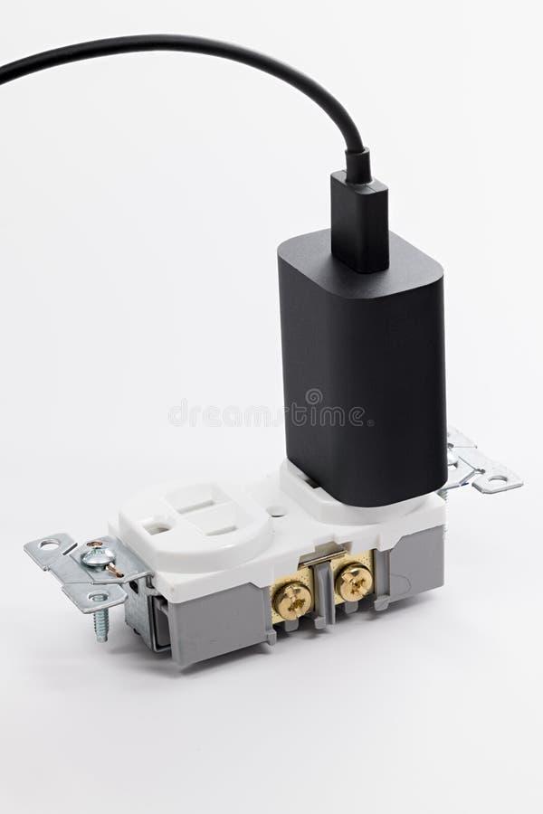 USB pluggar in ett elektriskt uttag på en tabletop royaltyfri bild