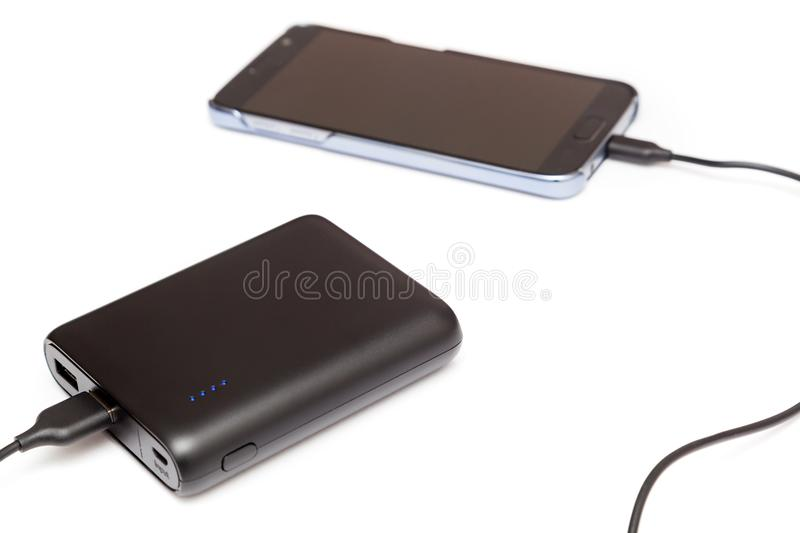 USB Power bank charging smartphone. On white stock photography