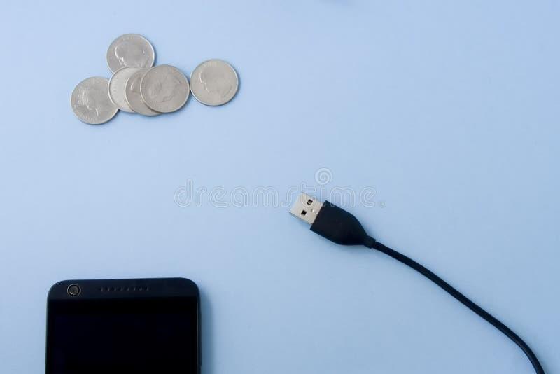 USB-stop met mobiele telefoon en geldmuntstukken op lichte pa's royalty-vrije stock afbeelding