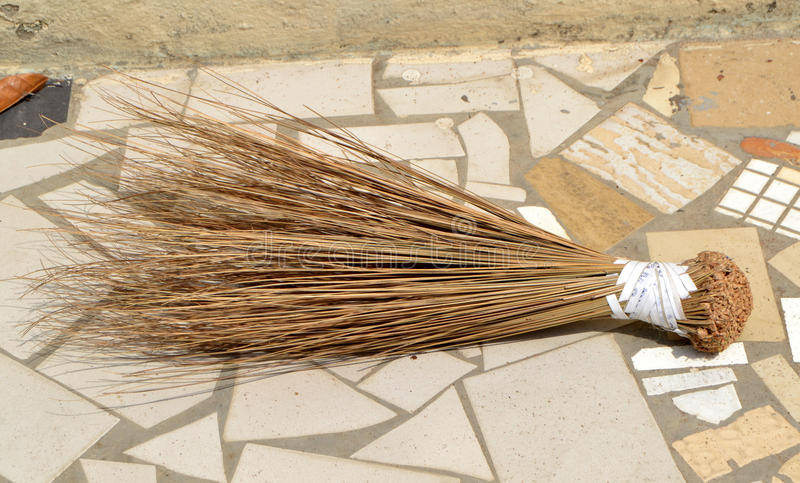 Use of the African broomstick. It is made from the apical bud of the palm species commonly called raffia palm. The tender leaves of this bud are dried and then stock image