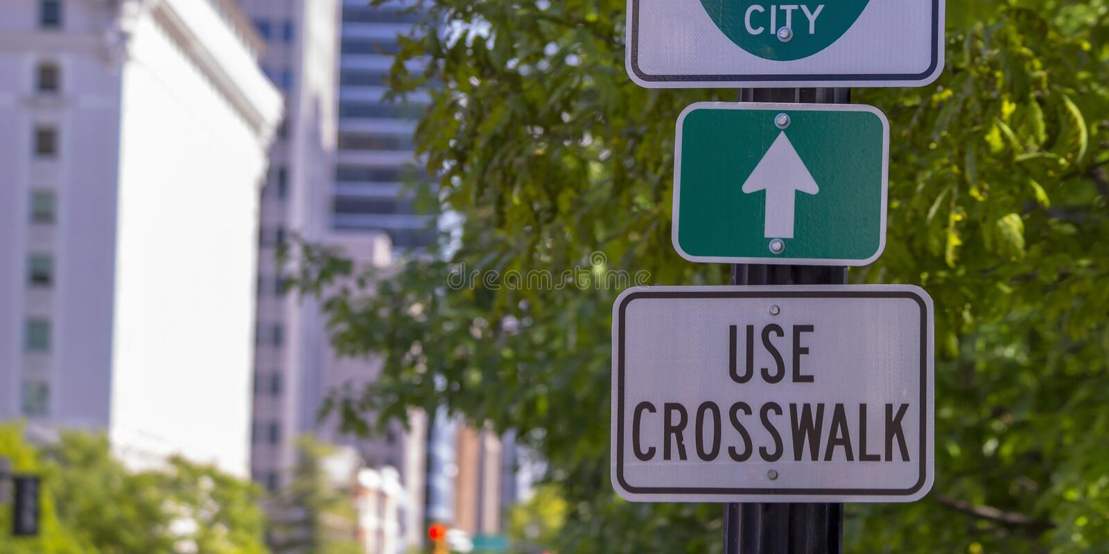 Use crosswalk and arrow signs on a sunny street. Close up view of road signs against a tree and buildings. One sign reads Use Crosswalk, while the other shows stock image