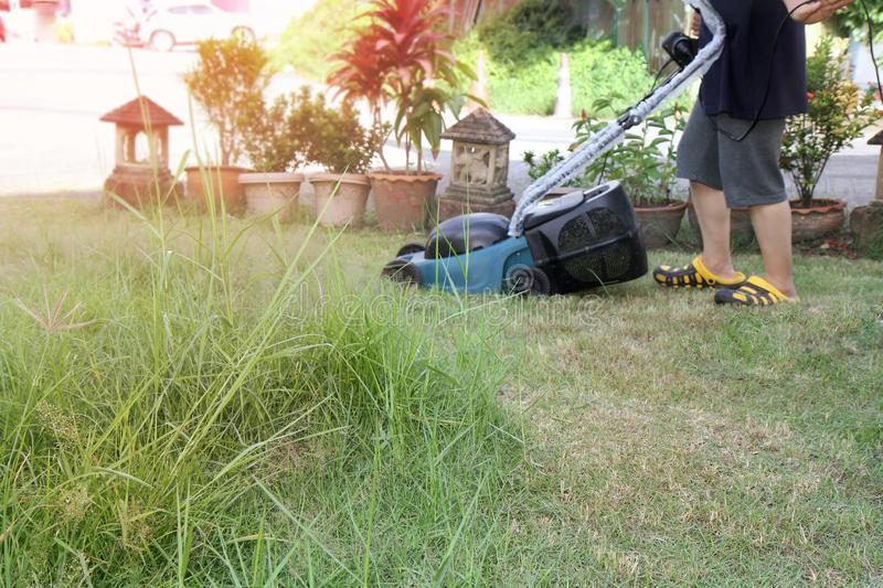 Use hands to push mower to cut the grass in greenary area of  house. Use hands to push mower to cut the grass in garden of  house stock image