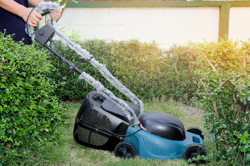 Use hands to push mower to cut the grass in greenary area of  house. Use hands to push mower to cut the grass in garden of  house stock images
