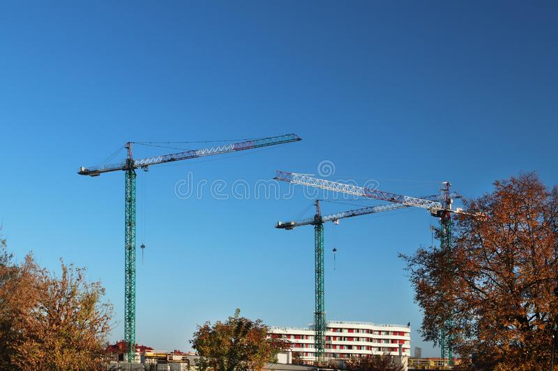 Use of high tower frame metal cranes in construction. Panorama of the development of the city against the blue sky. Work in real e. State and urbanization. Metal stock image