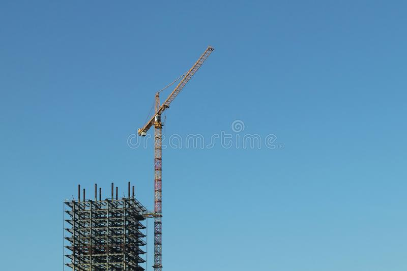 Use of high tower frame metal cranes in construction. Panorama of the development of the city against the blue sky. Work in real. Estate and urbanization. Metal stock images