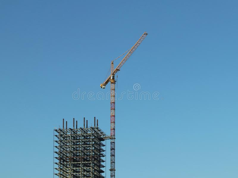 Use of high tower frame metal cranes in construction. Panorama of the development of the city against the blue sky. Work in real. Estate and urbanization. Metal stock photography