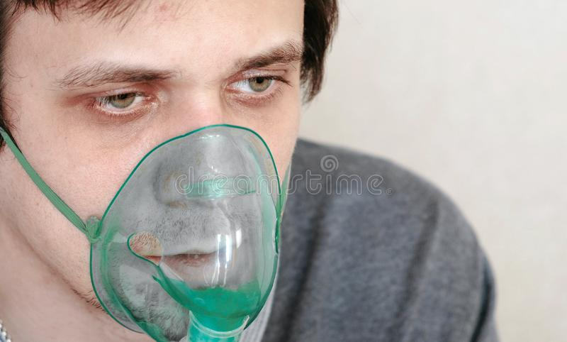 Use nebulizer and inhaler for the treatment. Closeup young man`s face inhaling through inhaler mask. Front view. royalty free stock photography
