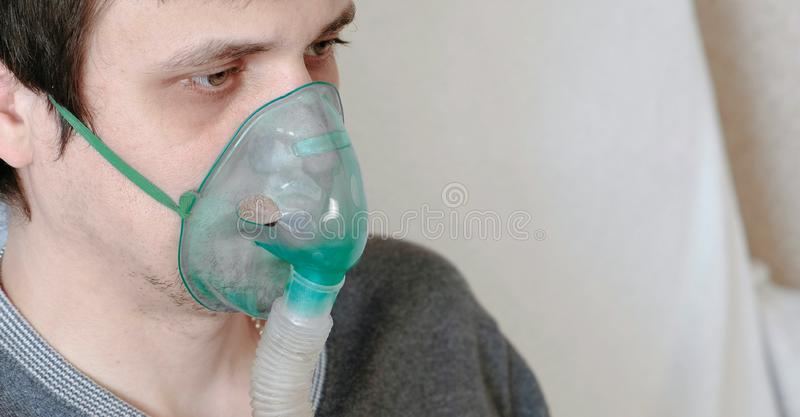 Use nebulizer and inhaler for the treatment. Closeup young man`s face inhaling through inhaler mask. Side view. stock image