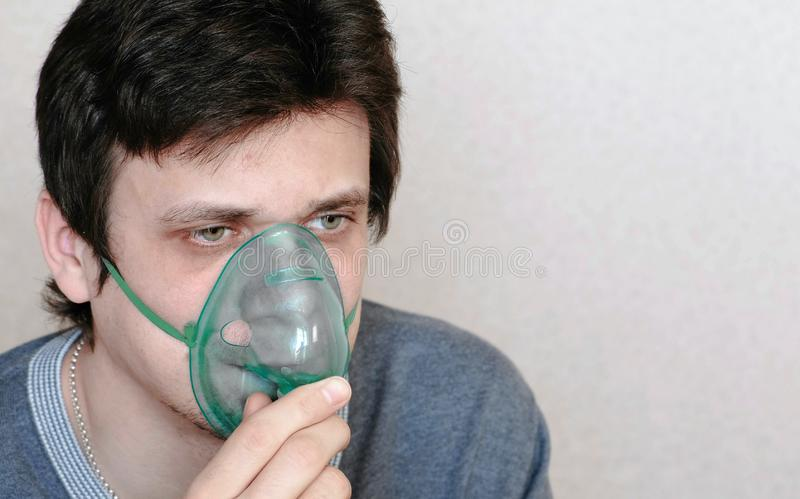 Use nebulizer and inhaler for the treatment. Young man inhaling through inhaler mask. Front view royalty free stock photo
