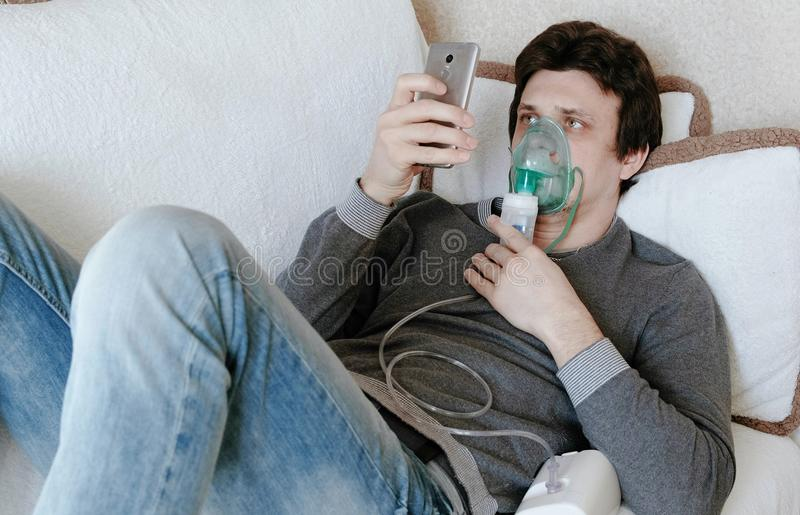Use nebulizer and inhaler for the treatment. Young man inhaling through inhaler mask lying on the couch and chatting in. Mobile phone. Side view stock images