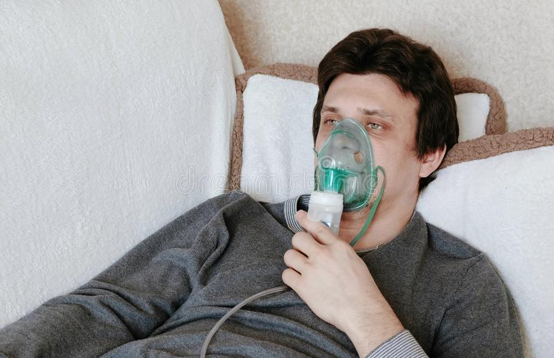 Use nebulizer and inhaler for the treatment. Young man inhaling through inhaler mask lying on the couch. Side view. royalty free stock images