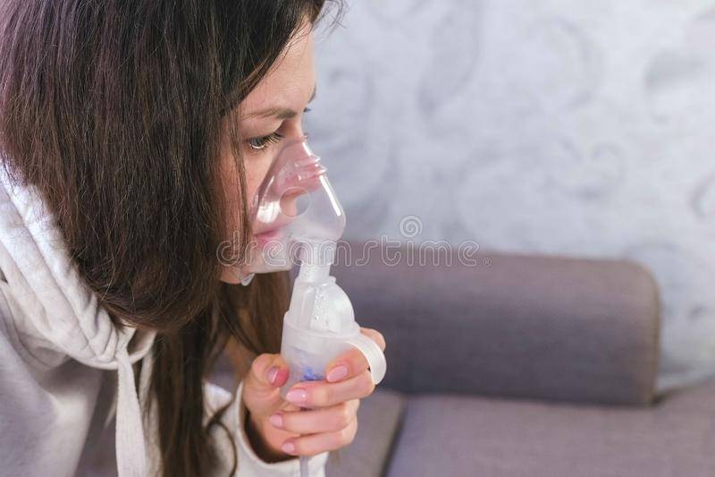 Use nebulizer and inhaler for the treatment. Young woman inhaling through inhaler mask, face close-up, side view. Use nebulizer and inhaler for the treatment stock photo