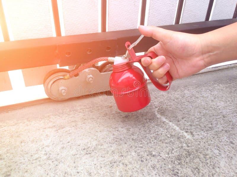Use o lubrificador para lubrificar as rodas da porta foto de stock