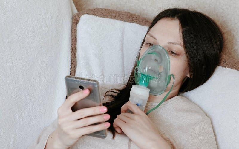 Use o nebulizer e o inalador para o tratamento Jovem mulher que inala através da máscara do inalador que encontra-se no sofá e na foto de stock royalty free