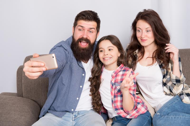 Use smartphone for selfie. Friendly family having fun together. Mom dad and daughter relaxing on couch. Family posing stock photo
