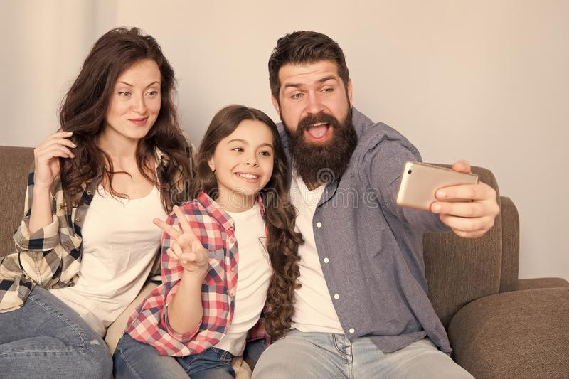 Use smartphone for selfie. Friendly family having fun together. Mom dad and daughter relaxing on couch. Family posing royalty free stock photo