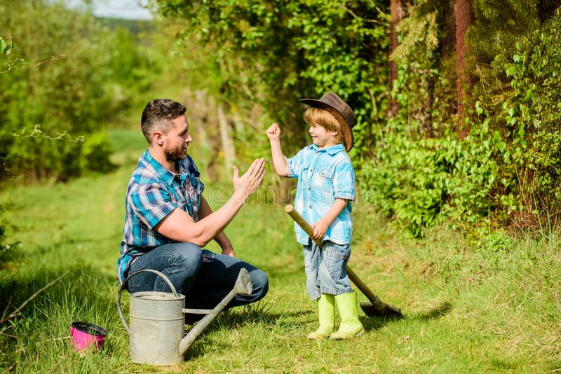 Use watering can and pot. Garden equipment. father and son in cowboy hat on ranch. Eco farm. happy earth day. Family stock photography
