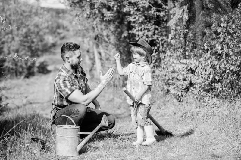 Use watering can and pot. Garden equipment. father and son in cowboy hat on ranch. Eco farm. happy earth day. Family royalty free stock images