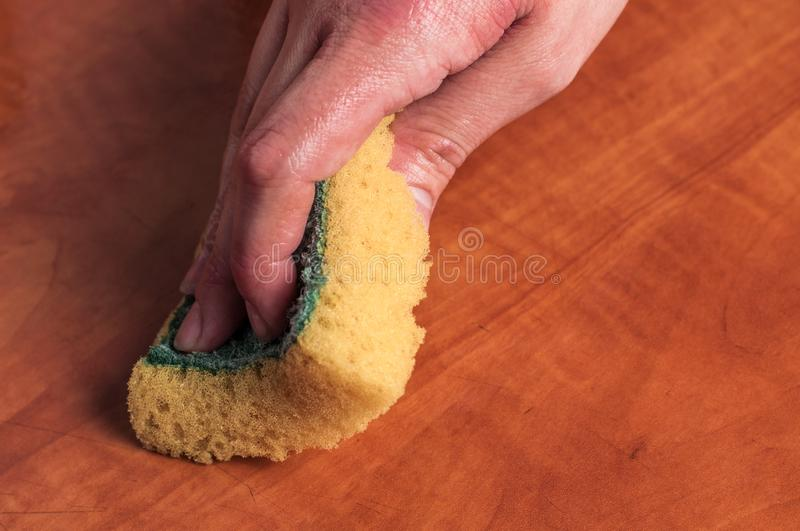 Use of a yellow sponge to clean the kitchen red table . Cleaning sponge stock image