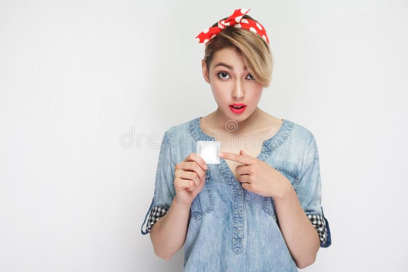 Use you? Portrait of worry beautiful young woman in casual denim shirt and red headband standing, holding condom and pointing stock photography