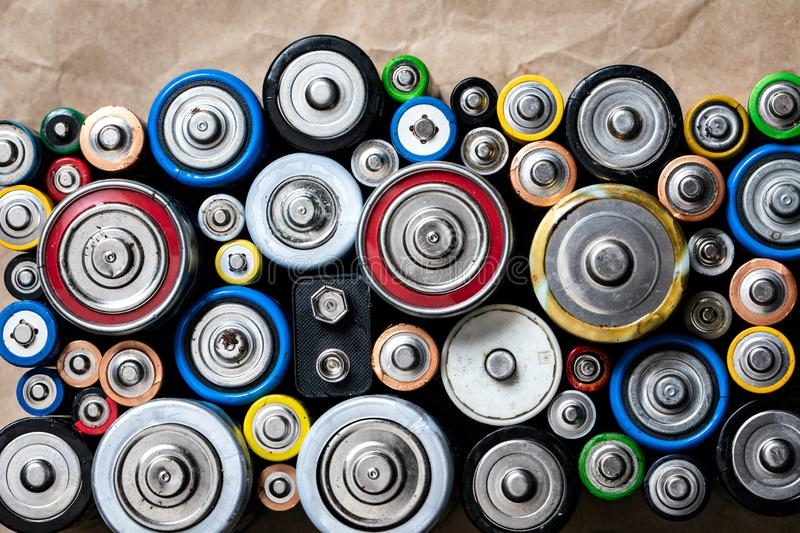 Used Alkaline batteries on recycled paper toxic waste recycling and ecology issues concept background. Used Alkaline batteries of various types C AA AAA D 9V on royalty free stock photo