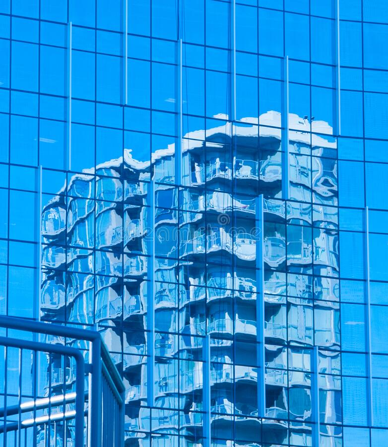 Reflection of a blue coloured highrise in the windows of another building royalty free stock photos