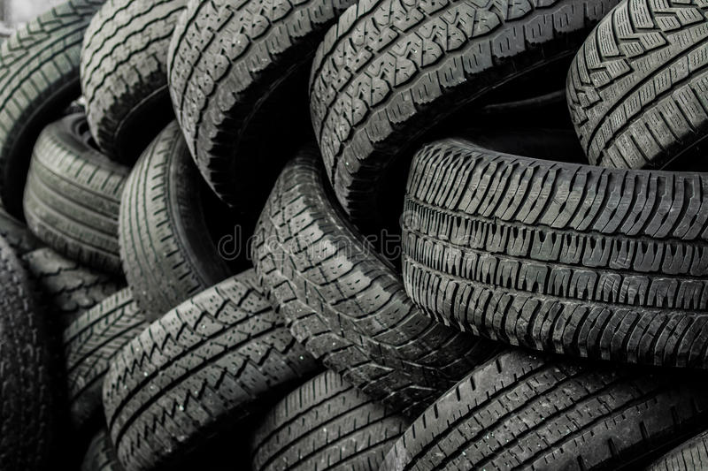 Used auto tires stacked in piles. Worn auto tires stacked at recycling facility stock photography