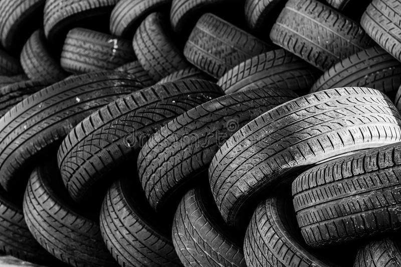 Used auto tires stacked in piles. Worn auto tires stacked at recycling facility stock image