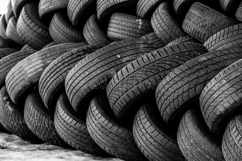 Used auto tires stacked in piles. Worn auto tires stacked at recycling facility royalty free stock photo