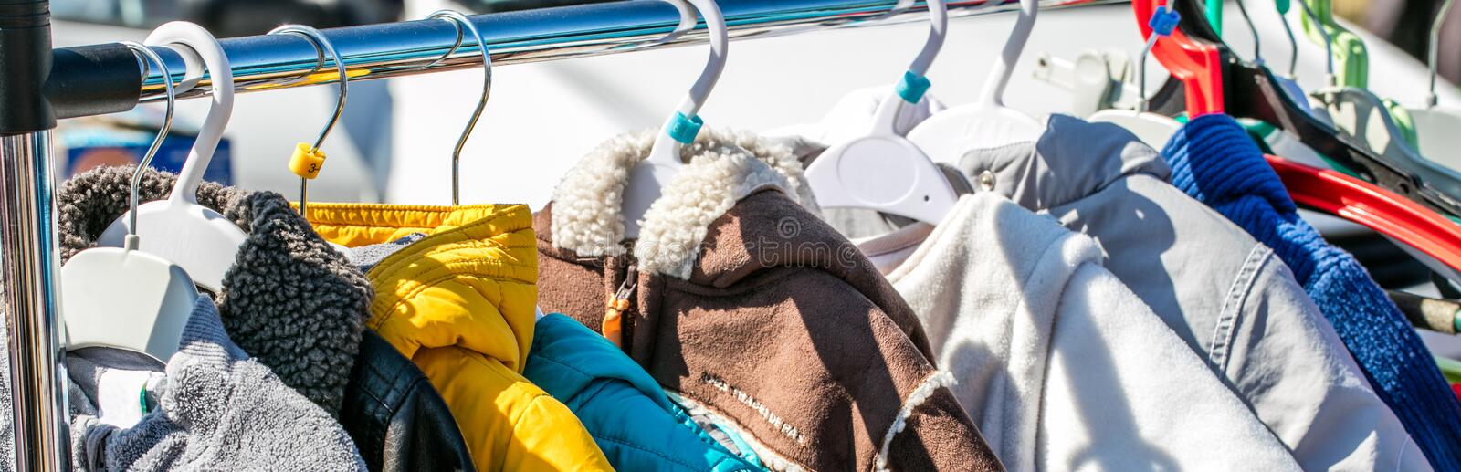 Used baby winter clothes, jackets and coats displayed on rack royalty free stock photo