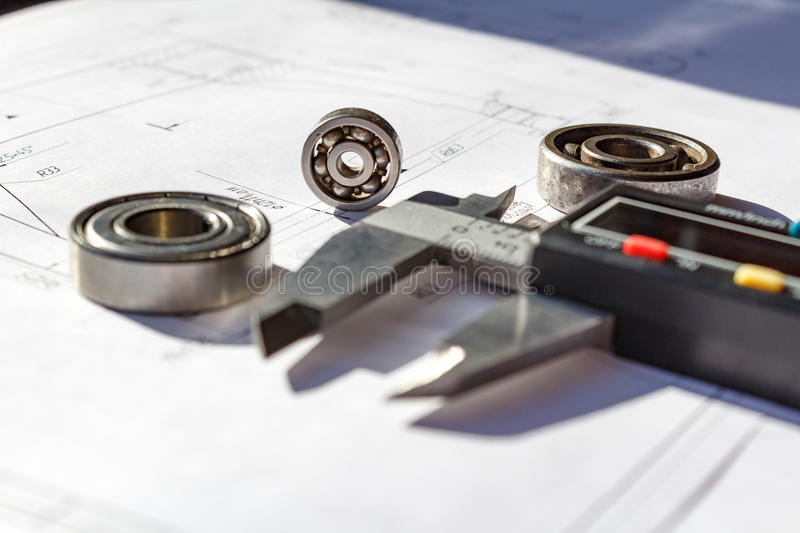Used ball bearings and electronic calipers on a table closeup stock photos