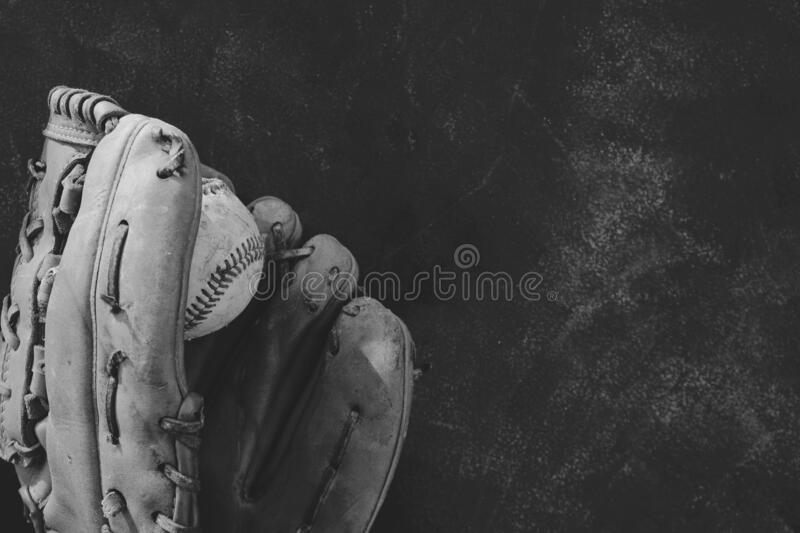 Monochrome baseball sports background. Used baseball glove with ball on background, copy space for sports concept in black and white stock photos