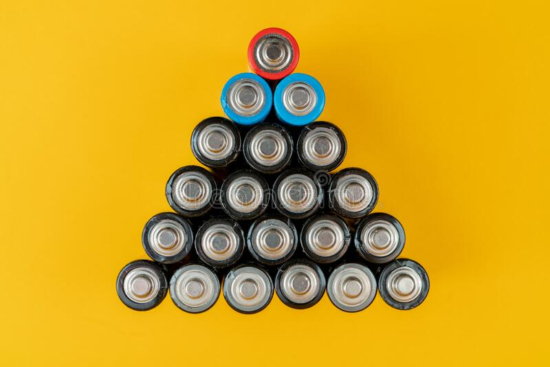 Used batteries are arranged in a triangle shape. Recycling and disposal of toxic waste royalty free stock image