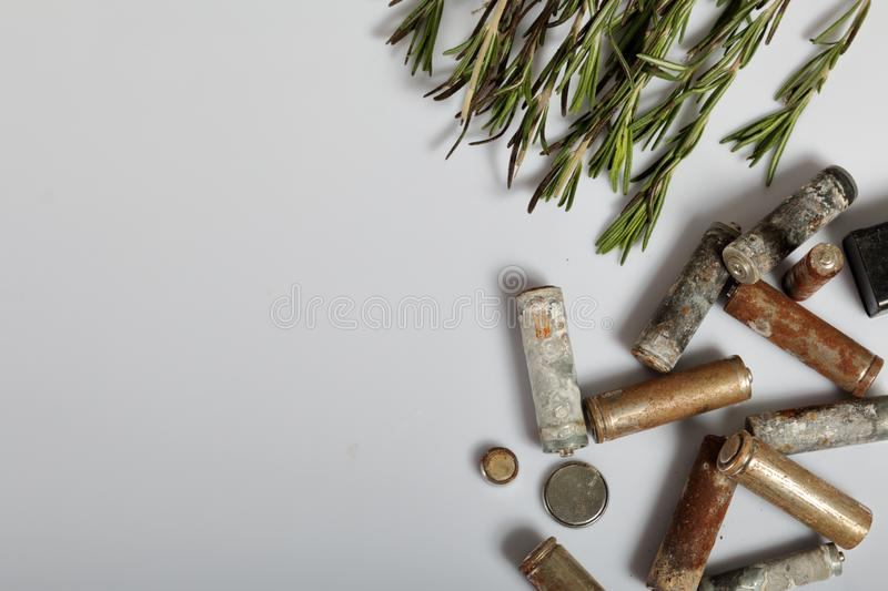 Used batteries and a branch of greens. Recycling waste batteries. Environmental Protection. Earth Day.  royalty free stock photo