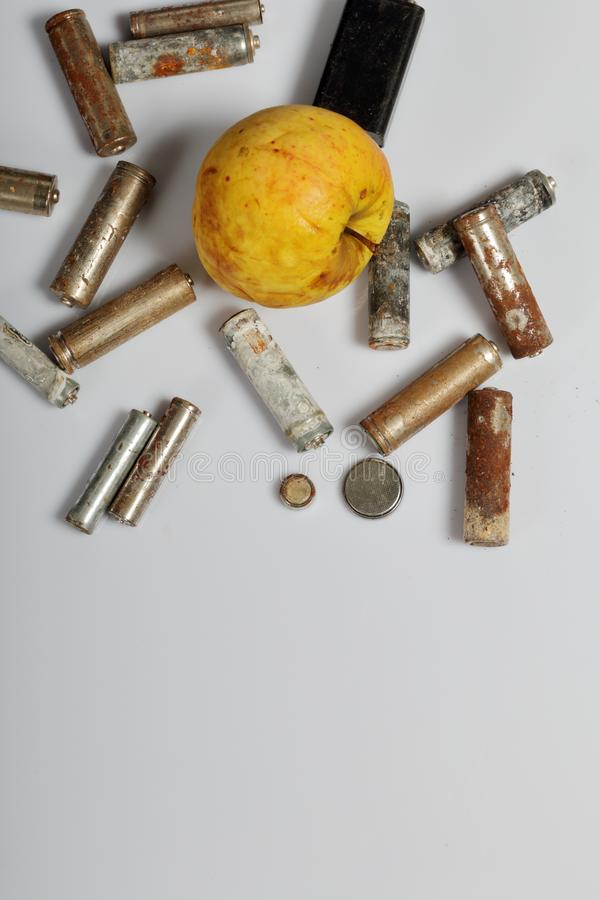 Used batteries and faded apple. Recycling waste batteries. Environmental Protection. Earth Day.  stock image