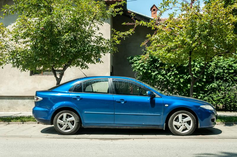 Used blue Mazda 6 car parked on the street in the city stock photography