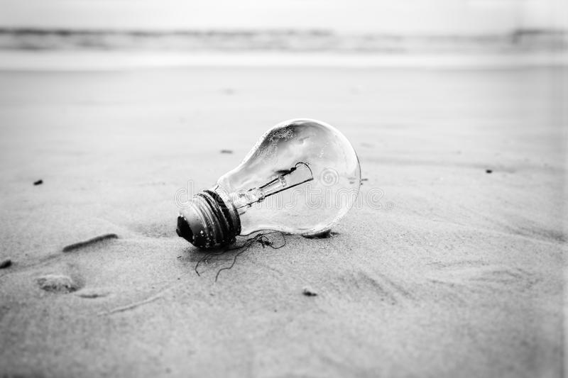 Burnt Light Bulb on a Beach. A used burnt-out incandescent light bulb abandoned on a sandy beach in inclement weather. Relates to energy conservation and stock photo
