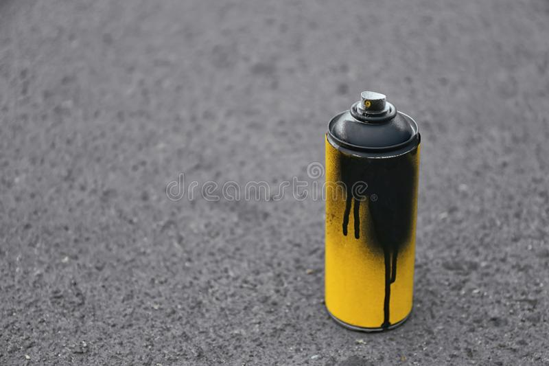 Used can of spray paint on asphalt. Space for text stock photo