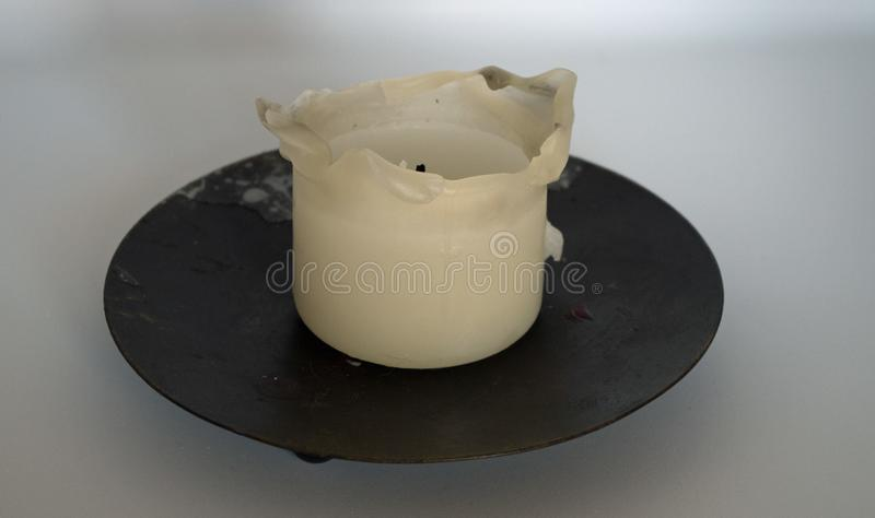 Used candle white on balck candleholder on white background. Home decoring natural light oriental parfum decoration stock photography
