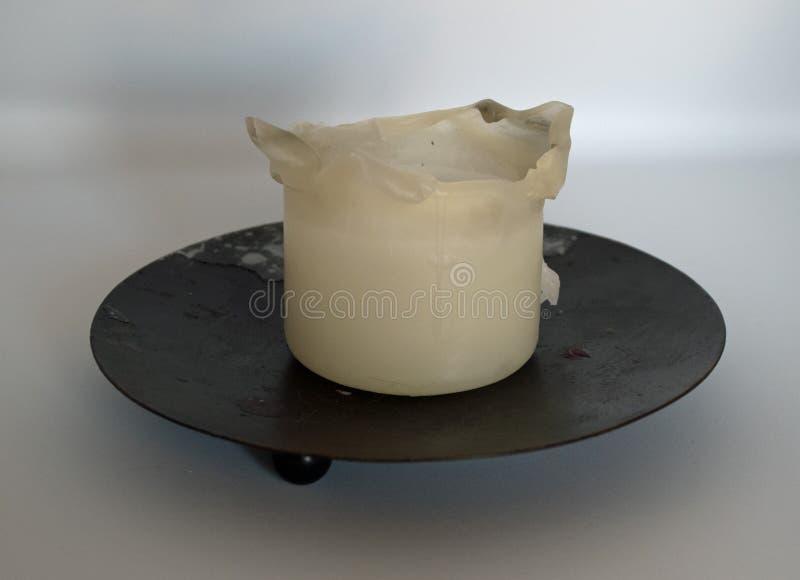 Used candle white on balck candleholder on white background. Home decoring natural light oriental parfum decoration stock image