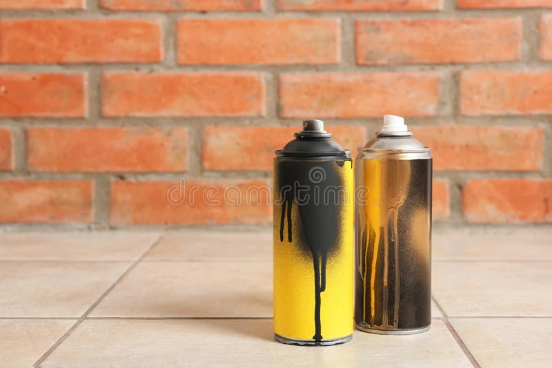 Used cans of spray paint on floor against brick wall. stock photo