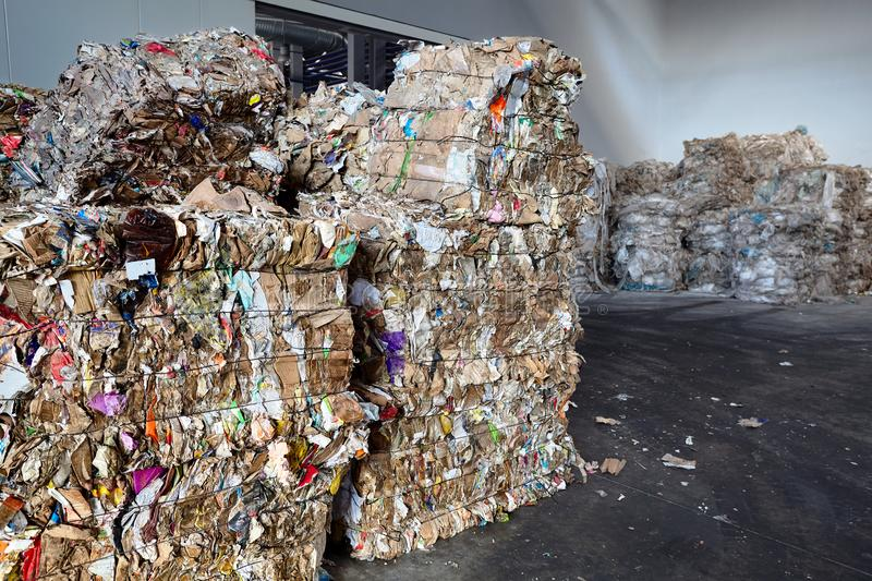 Used cardboard polyethylene and plastic pressed into bales at finished products warehouse on modern waste sorting and processing stock photo