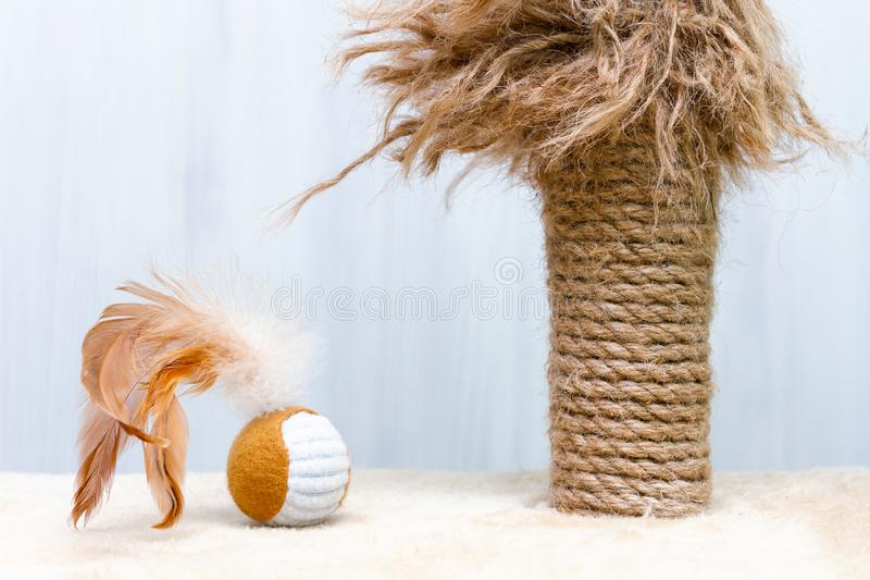 Used cat scratching post with ragged parts and cat toy round ball with a feathers on white background.  stock images