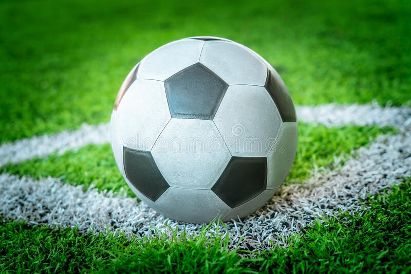 Classic black and white soccer ball on football corner marking field with no people stock photos