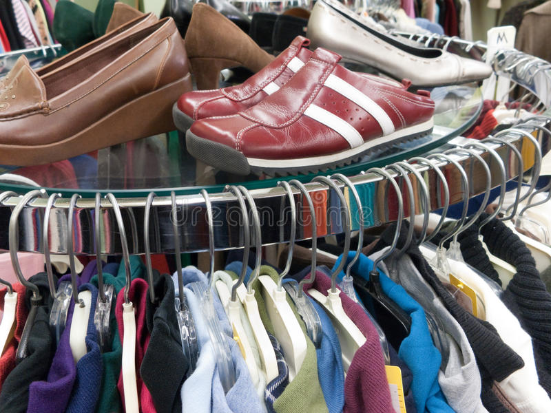 Used Clothing and Shoes at Thrift Store. Rack with used or consignment clothing and shoes at thrift store royalty free stock photography