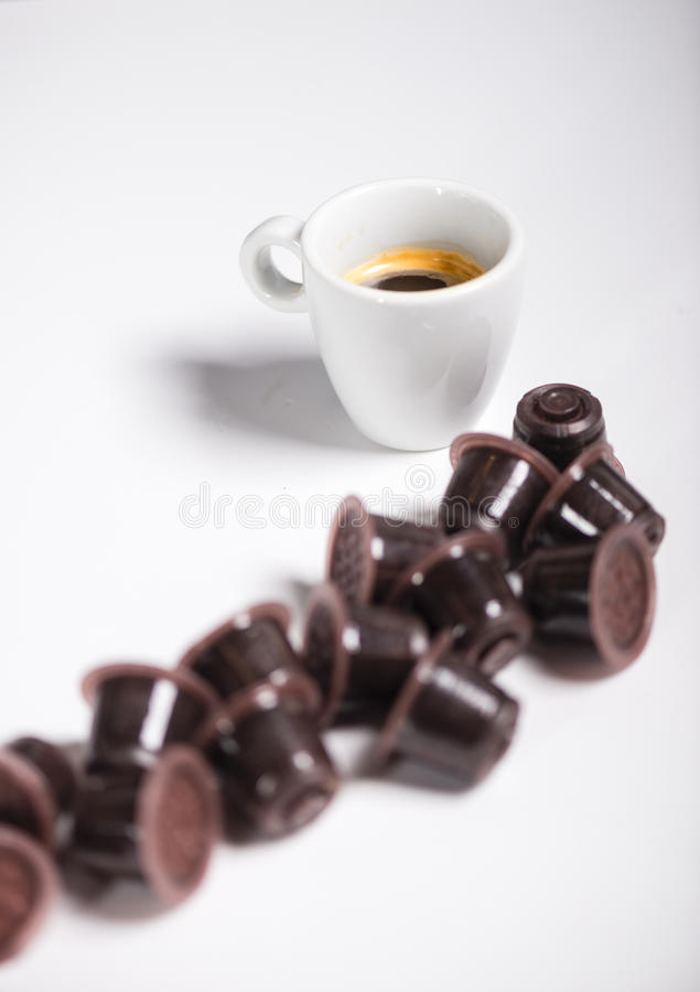 Used coffe capsules and espresso coffee over a white background. stock photo