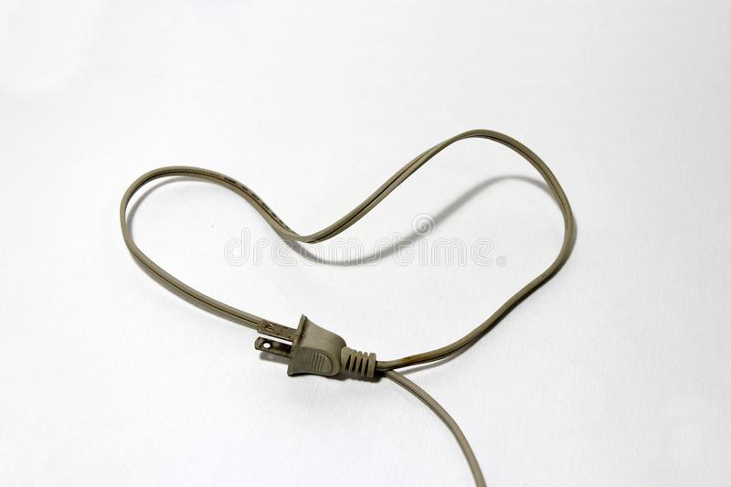Used cream color of plug with cable put like a heart on the white floor, love concept of electrician. royalty free stock photography