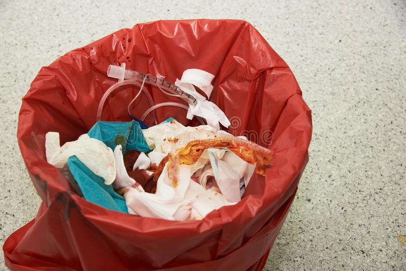 Used endotracheal tube, surgical gloves stained with blood in a red garbage bin. For biohazard disposal stock images